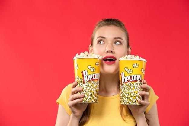Vorderansicht junge frau im kino, die popcorn-paket auf dem hellroten wandkino-kinokino-spaßfilm der frau hält