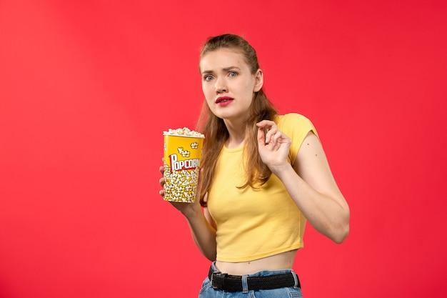 Vorderansicht junge frau im kino hält popcorn-paket auf rote wand filme theater kino snack frau spaß film