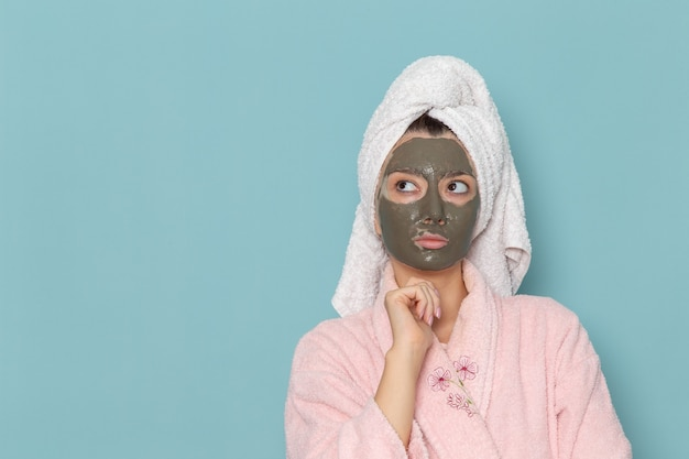 Vorderansicht junge frau im rosa bademantel mit maske auf ihrem gesicht, das an die blaue wanddusche denkt, die schönheits-selbstpflegecreme reinigt