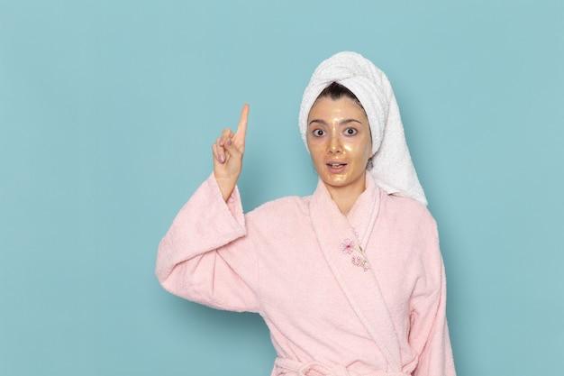 Vorderansicht junge frau im rosa bademantel nach der dusche auf hellblauer wand schönheit wasserbad creme selbstpflege dusche