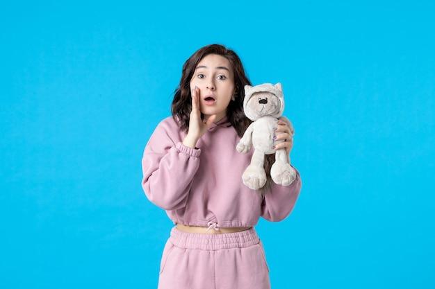Vorderansicht junge frau im rosa pyjama mit kleinem spielzeugbär auf blauer farbe