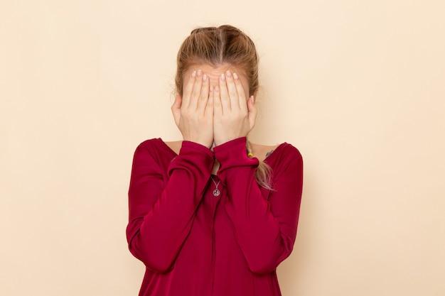 Vorderansicht junge frau im roten hemd, das ihr gesicht auf dem häuslichen foto oclor der cremeraum-gefühlsgewalt bedeckt