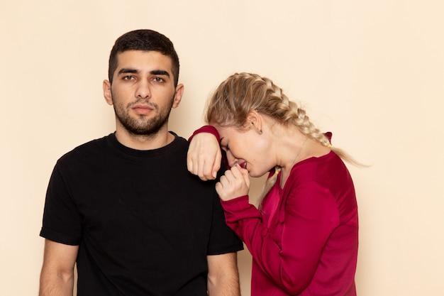 Vorderansicht junge frau im roten hemd, das in die schultern des mannes auf dem weiblichen foto des cremefarbenen raumes weint