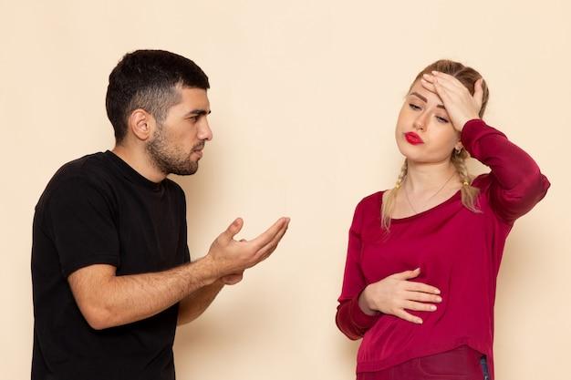 Vorderansicht junge frau im roten hemd, das mit jungem mann auf der konfrontation des weiblichen stoff-quarells des cremefarbenen raums stritt