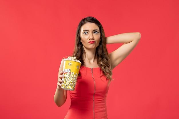 Vorderansicht junge frau im roten hemd, das popcorn hält und auf roter oberfläche denkt