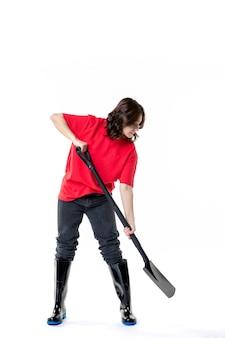 Vorderansicht junge frau im roten hemd imitiert das graben mit schwarzer schaufel auf weißem hintergrund bodenfarbe arbeit frau emotion friedhof boden job