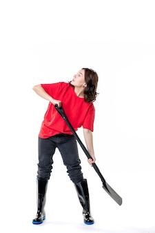 Vorderansicht junge frau im roten hemd imitiert das graben mit schwarzer schaufel auf weißem hintergrund bodenfarbe arbeit frau friedhof boden job
