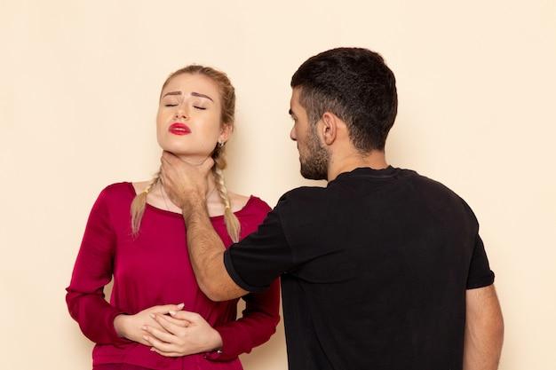 Vorderansicht junge frau im roten hemd leidet unter physischen bedrohungen und gewalt auf dem cremefarbenen weiblichen foto
