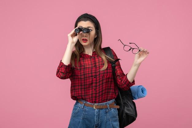 Vorderansicht junge frau im roten hemd mit fernglas auf rosa schreibtischfrau fotomodell