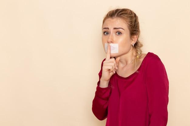 Vorderansicht junge frau im roten hemd mit gebundenem mund, der schweigezeichen auf dem weiblichen stofffoto des cremeraums zeigt