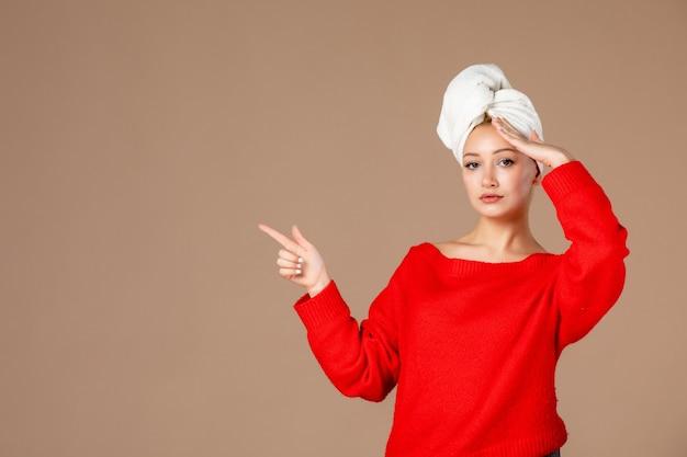 Vorderansicht junge frau im roten hemd mit handtuch auf dem kopf auf brauner wand