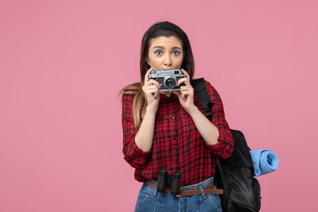 Vorderansicht junge frau im roten hemd mit kamera auf der rosa hintergrundmodellfotofrau