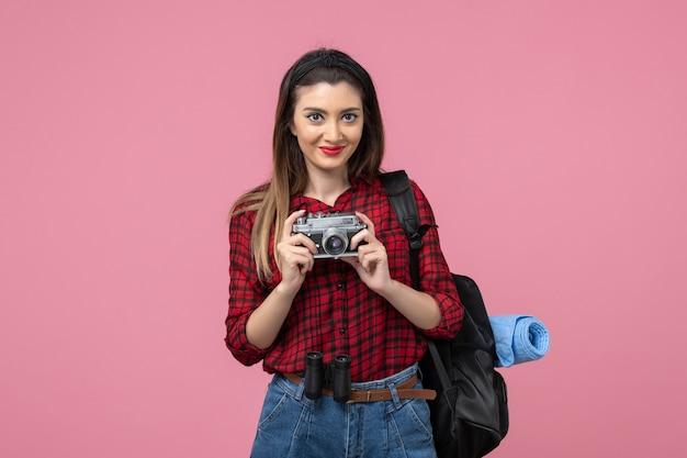 Vorderansicht junge frau im roten hemd mit kamera auf rosa schreibtischmodellfotofrau