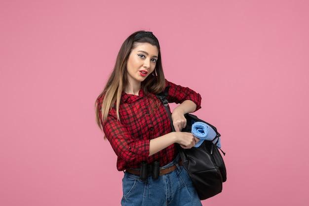 Vorderansicht junge frau im roten hemd mit tasche auf dem rosa hintergrundfrauenfotomodell