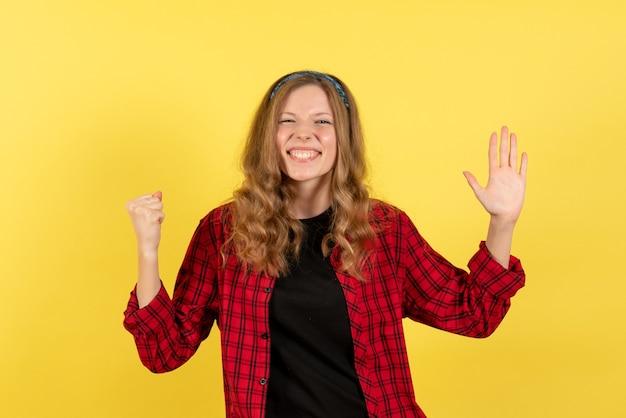 Vorderansicht junge frau im roten karierten hemd, das auf menschlichem farbmodellfrau des gelben hintergrundmädchen steht