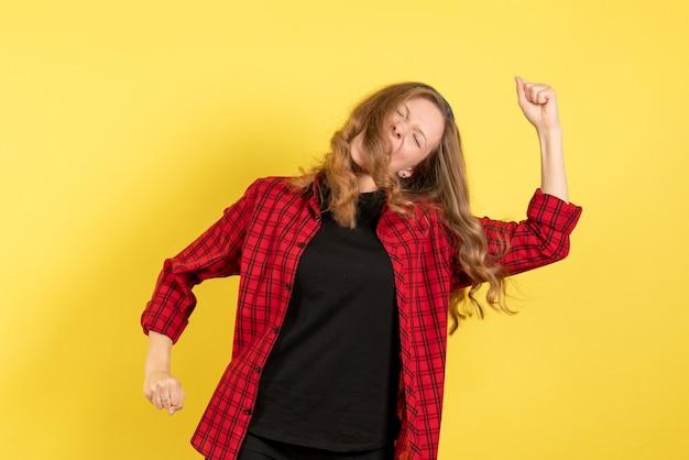Vorderansicht junge frau im roten karierten hemd, das auf menschlichem farbmodellfrauengefühl des gelben hintergrunds aufwirft und tanzt