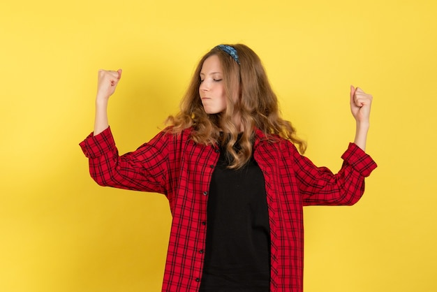 Vorderansicht junge frau im roten karierten hemd, das gerade auf menschlichem farbmodellfrau des gelben hintergrundmädchens steht