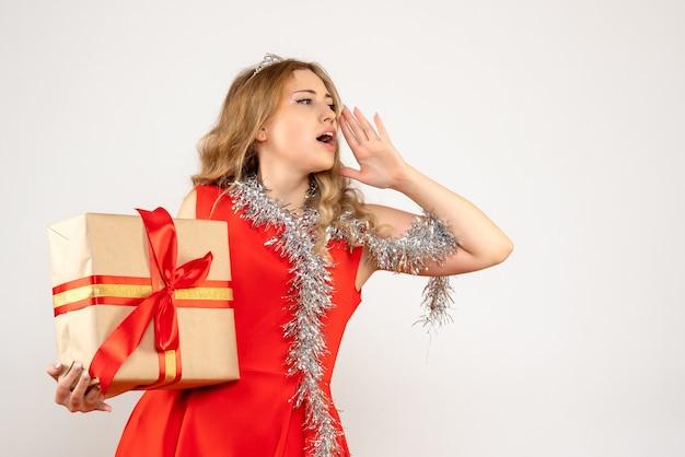 Vorderansicht junge frau im roten kleid, das weihnachtsgeschenk hält und anruft