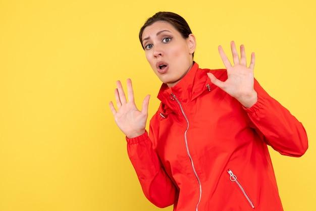 Vorderansicht junge frau im roten mantel auf gelbem hintergrund