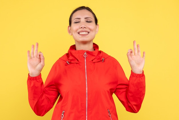 Vorderansicht junge frau im roten mantel, der auf gelbem hintergrund meditiert