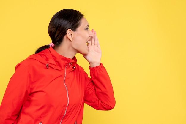 Vorderansicht junge frau im roten mantel, der gelben hintergrund anruft
