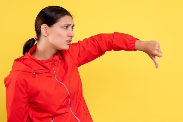 Vorderansicht junge frau im roten mantel missfiel auf gelbem hintergrund