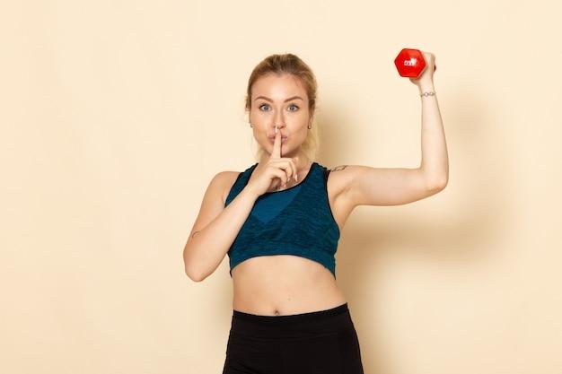 Vorderansicht junge frau im sportoutfit, das hanteln auf weißer wand hält sportkörpergesundheitsschönheitstrainingsfrau