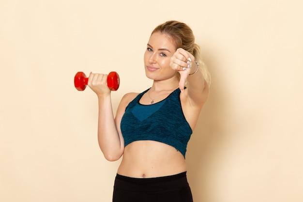 Vorderansicht junge frau im sportoutfit, das rote hanteln auf hellweißem wandgesundheitssportkörperschönheitstraining hält