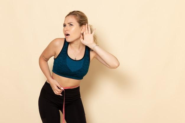 Vorderansicht junge frau im sportoutfit, die ihren körper misst und zuhört