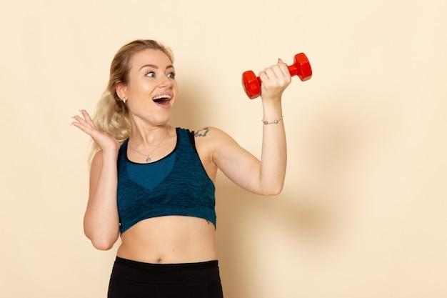 Vorderansicht junge frau im sportoutfit, die rote hanteln auf der hellen weißen wand sportkörpergesundheitsschönheitstraining hält