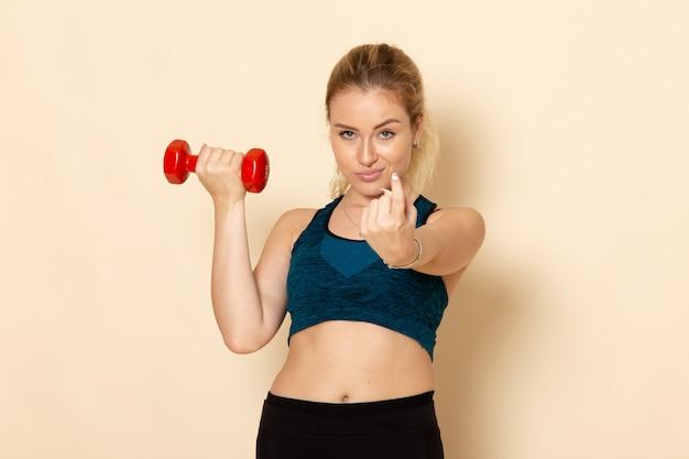Vorderansicht junge frau im sportoutfit, die rote hanteln auf weißem wandgesundheitssportkörperschönheitstraining hält
