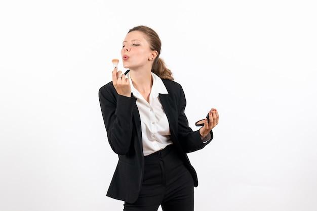 Vorderansicht junge frau im strengen klassischen anzug, der ihr make-up auf weißem schreibtischfrauenjobkostümgeschäft ernst macht