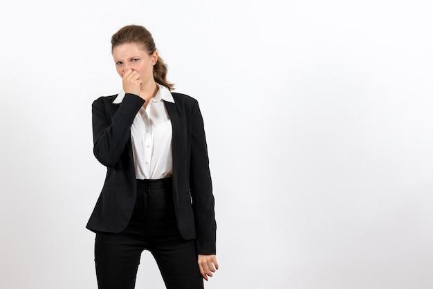 Vorderansicht junge frau im strengen klassischen anzug, der ihre nase auf weißem hintergrundjobfrau-geschäftsfrauenanzugarbeit schließt