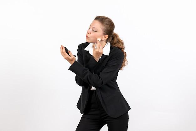 Vorderansicht junge frau im strengen klassischen anzug, der make-up auf weißem hintergrundfrauenjob ernstes kostümgeschäft tut