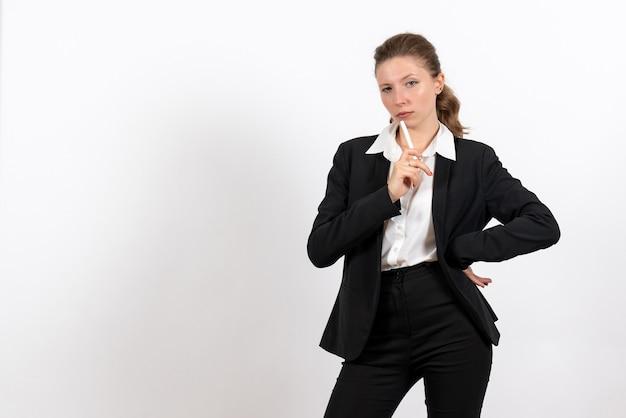 Vorderansicht junge frau im strengen klassischen anzug, der stift auf weiblichem arbeitskostüm des frauenberufsgeschäfts des weißen hintergrunds hält