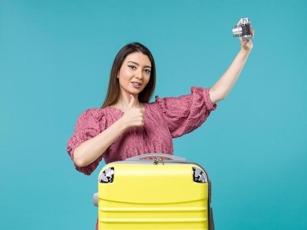 Vorderansicht junge frau im urlaub, die foto mit kamera auf blauem hintergrund reisefrau im ausland seeurlaub macht