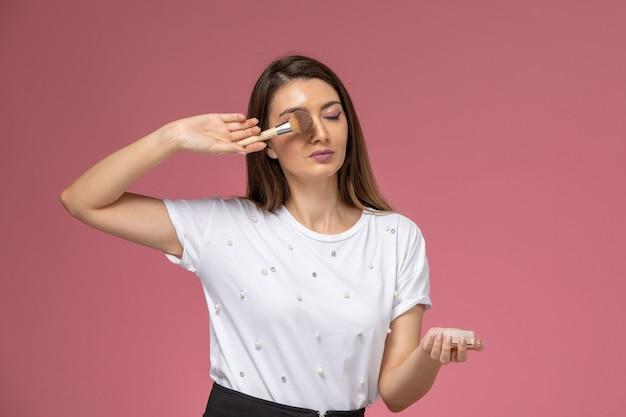Vorderansicht junge frau im weißen hemd, das bürste für make-up, schönheit hält