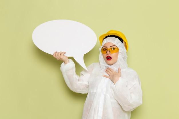 Vorderansicht junge frau im weißen sonderanzug und im gelben helm, der großes weißes zeichen auf der grünraumchemiearbeit hält