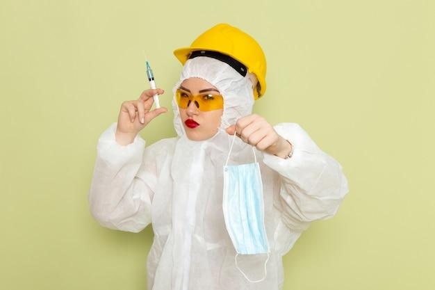 Vorderansicht junge frau im weißen sonderanzug und im gelben helm, der injektion und maske auf der grünfläche hält
