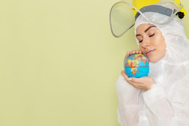 Vorderansicht junge frau im weißen sonderanzug und im gelben helm, der kleinen globus auf der grünfläche hält