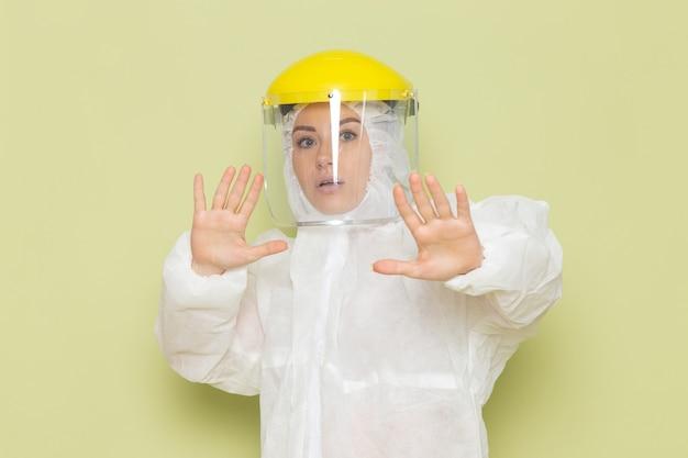 Vorderansicht junge frau im weißen sonderanzug und im gelben helm, der mit vorsicht auf der einheitlichen wissenschaft des grünraumanzugs aufwirft