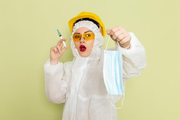 Vorderansicht junge frau im weißen sonderanzug und im gelben helm, der sterile maske auf der grünfläche hält