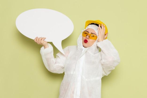 Vorderansicht junge frau im weißen sonderanzug und im gelben helm, der weißes zeichen mit leichtem lächeln auf der chemie der grünfläche hält