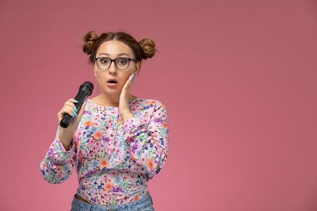 Vorderansicht junge frau in blume entworfenes hemd und blaue jeans, die mikrofon halten versuchen, auf dem rosa hintergrund zu singen