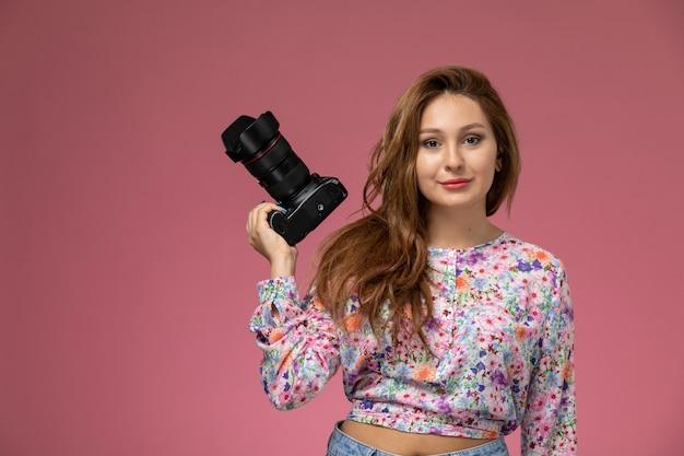 Vorderansicht junge frau in blume entworfenes hemd und blaue jeans lächelnde haltekamera auf rosa hintergrund