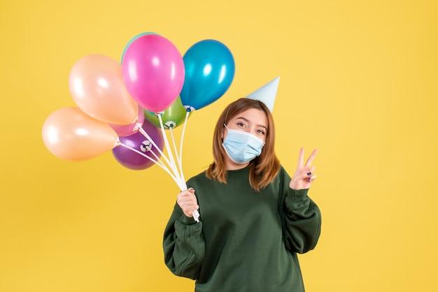 Vorderansicht junge frau in der maske, die bunte luftballons hält