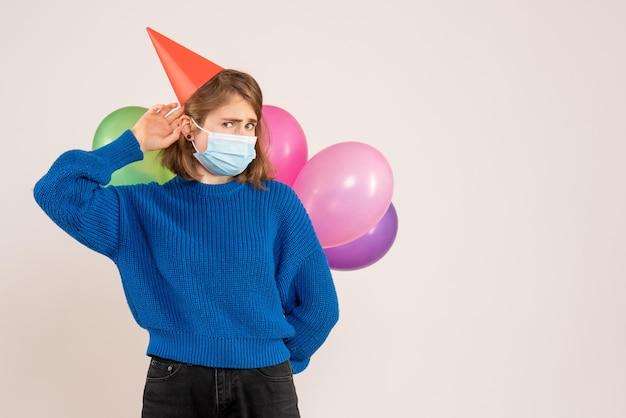 Vorderansicht junge frau in der maske, die bunte luftballons hinter ihrem rücken hält