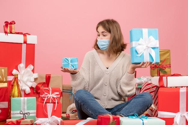 Vorderansicht junge frau in der maske, die um weihnachtsgeschenke sitzt