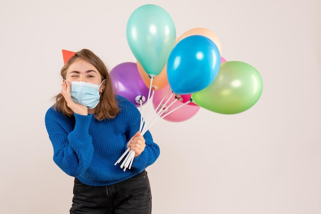 Vorderansicht junge frau in der sterilen maske, die bunte luftballons hält