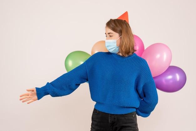 Vorderansicht junge frau in der sterilen maske, die bunte luftballons hinter ihrem rücken versteckt
